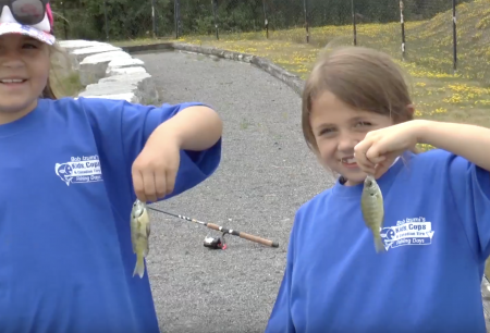 two girls holding up little fish they caught